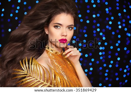 Makeup. Long Hair. Fashion woman portrait. Beautiful brunette girl model with sensual lips, long wavy hairstyle over holiday Christmas blue lights background. - stock photo