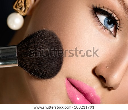 Makeup. Make-up Applying closeup. Cosmetic Powder Brush for Make up. Beauty Girl with Perfect Skin. Blue eyes, Pink Lipstick. Isolated on Black Background. Makeover  - stock photo