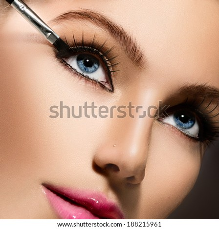 Makeup. Make-up Applying closeup. Eyeliner. Cosmetic Eyeshadows. Eyeline brush for Make up. Beauty Girl with Perfect Skin. Eyelashes. Blue eyes, Pink Lipstick. Isolated on Black Background. Makeover  - stock photo