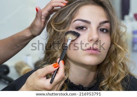 makeup makes a girl in a beauty salon