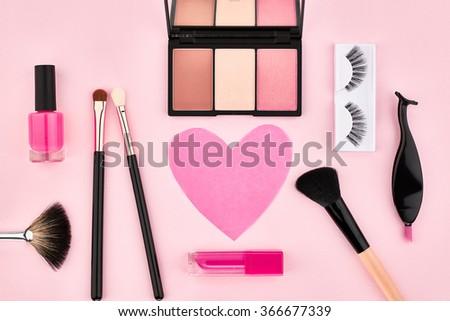 Makeup Overhead fashion woman makeup essentials cosmetics. Beauty makeup accessories. Lipstick, brushes, eyeshadow, false eyelashes, heart.Unusual creative makeup set. Pink background, makeup top view - stock photo