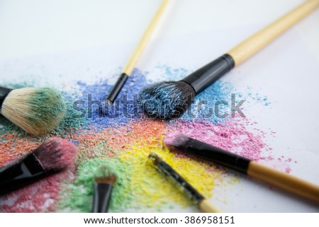 makeup powder and brush on white background, focused on light blue brush