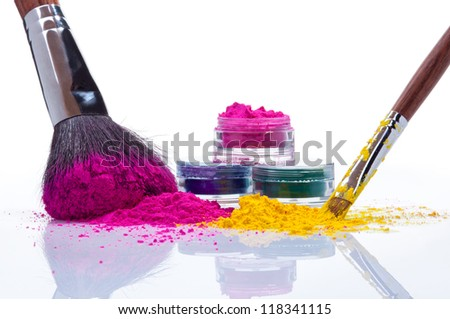 Makeup powder of different colors and brushes - stock photo
