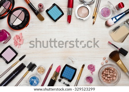 Makeup products on wooden background with copy space in center - stock photo
