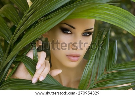 Makeup. Sexy beautiful woman hiding behind the palm leaves like a panther in the tropical forest in India. Portrait of beautiful caucasian stylish young woman with smokey eyes, wildness - stock photo