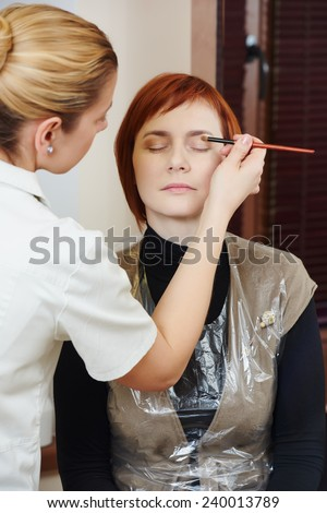 Makeup technique. Applying eye shadow on redheaded woman
