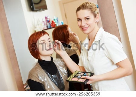 Makeup technique. specialist works with mascara eyelashes of redheaded woman in beauty salon - stock photo