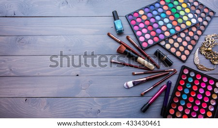 Makeup tools, lipstiks, nailpolish and colorful eyeshadow palettes on grey wooden table - stock photo
