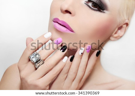 Makeup with pink lips and nail Polish with different colors of paint and rhinestones. - stock photo