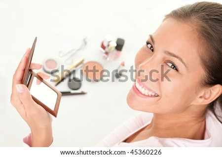 Makeup woman. Cute cosmetics woman having fun with make-up products. - stock photo
