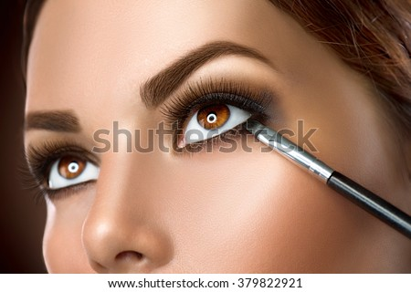 Makeup. Woman Make-up Applying closeup. Eyeliner. Cosmetic Eyeshadows. Eyeline brush for Make up. Beauty Girl with Perfect Skin. Eyelashes. Brown eyes. Makeover - stock photo
