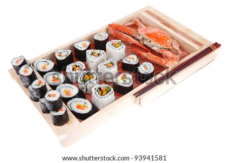 Maki Roll with Deep Fried Vegetables inside . on wooden plate with live crab . isolated over white background . Japanese Cuisine
