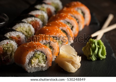 Maki rolls and nigiri sushi on a wooden table. Salmon, avocado and caviar rolls.