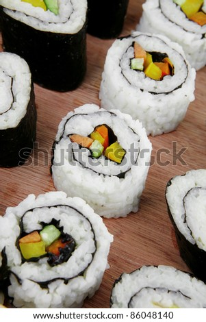 Maki Sushi and Nigiri - Maki Rolls and California rolls made of fresh raw Salmon, Tuna and Eel with Cream Cheese and Avocado . Isolated over white background . on wooden plate - stock photo