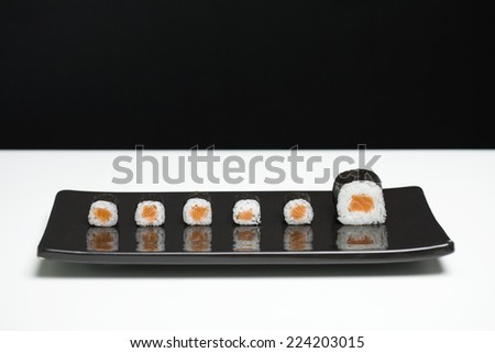 Maki sushi arranged on plate, one piece larger than the rest - stock photo