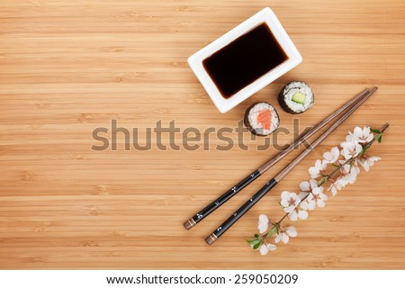 Maki sushi, chopsticks and soy sauce on bamboo wooden table background with copy space - stock photo
