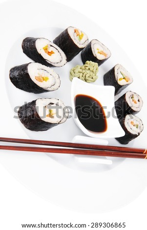 Maki Sushi : Maki Rolls and California rolls made of fresh raw Salmon(sake), Tuna(maguro) and Eel(unagi) . on white dish with sticks isolated over white background - stock photo