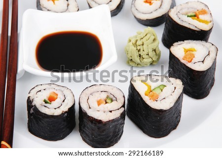 Maki Sushi : Maki Rolls and California rolls made of fresh raw Salmon(sake), Tuna(maguro) and Eel(unagi) . on white dish with sticks isolated over white background - stock photo