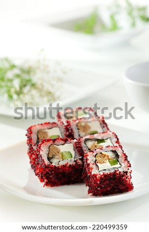 Maki Sushi - Roll made of Cream Cheese, Jjapanese omelet, Cucumber and Smoked Eel inside. Red and Black Tobiko outside - stock photo