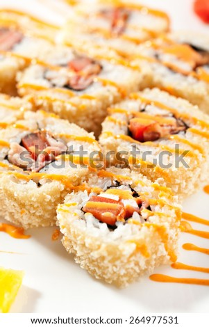 Maki Sushi - Roll made of Smoked Chicken Breast, Cheese and Tomato inside. Croutons outside. Garnished with Spicy Sauce