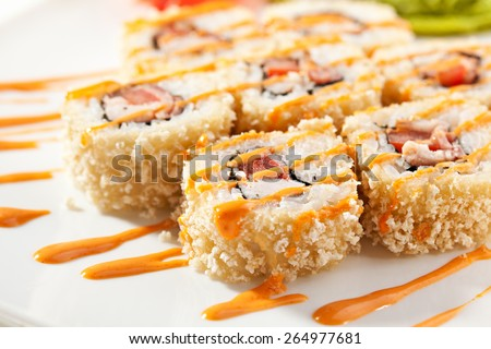 Maki Sushi - Roll made of Smoked Chicken Breast, Cheese and Tomato inside. Croutons outside. Garnished with Spicy Sauce - stock photo