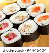 Maki Sushi - Roll made of Tuna, Salmon, Eel, Cream Cheese, Fruits and Vegetables inside. Nori outside - stock photo