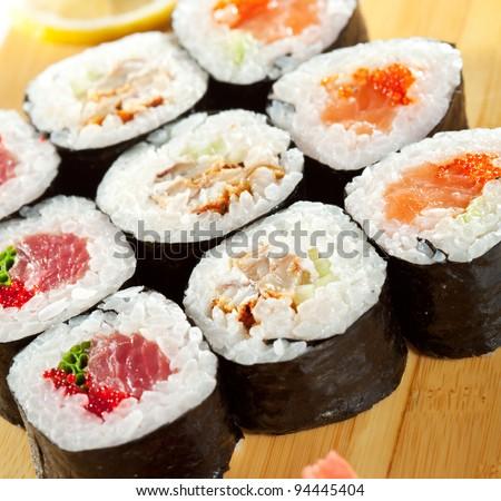 Maki Sushi - Roll made of Tuna, Salmon, Eel, Cream Cheese, Fruits and Vegetables inside. Nori outside - stock photo
