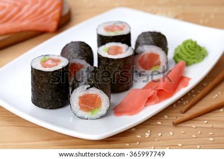 Maki sushi roll with salmon, wasabi, ginger and nori seaweed.  - stock photo