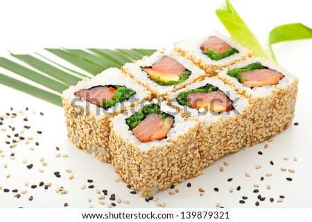 Maki Sushi - Roll with Smoked Salmon, Sweet Pepper, Salad Leaf and Chuka Seaweed inside. Sesame outside. Served with Banana Leaf - stock photo