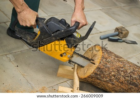 Making a birdhouse from alder logs with chainsaw - stock photo