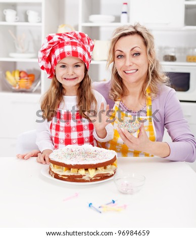 Making a cake for my birthday - little girl with mother in kitchen - stock photo