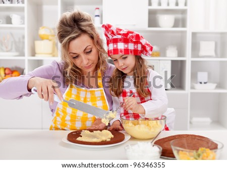 Making a cake together - woman and little girl in the kitchen - stock photo