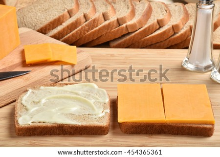 Making a cheddar cheese sandwich on a cutting board - stock photo