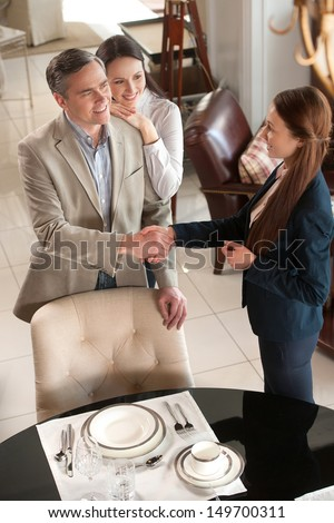 Making a deal. Cheerful middle-aged couple standing in furniture store while man shaking hand to sales clerk - stock photo