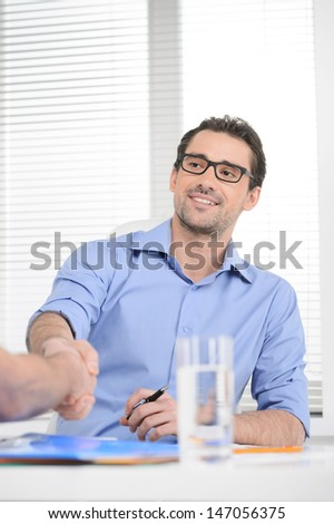 Making a deal. Young cheerful businessman shaking his business parner's hand - stock photo