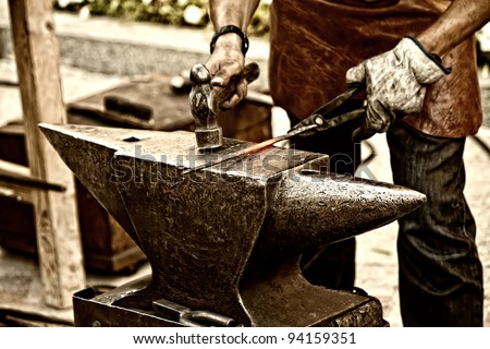 Making a decorative element in the smithy on the anvil - stock photo