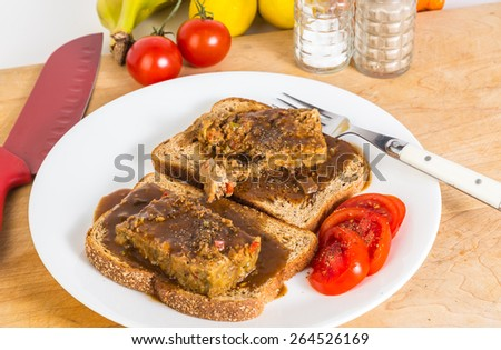 Making a meatloaf sandwich on whole grain toast smothered in brown gravy with sliced tomatoes. - stock photo