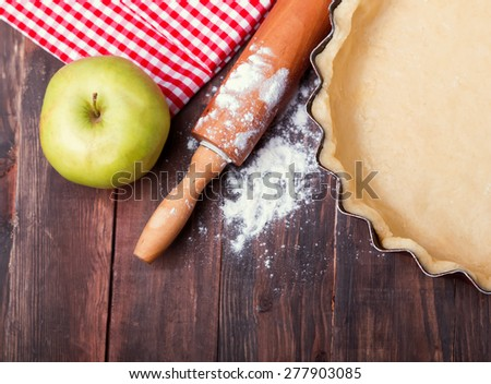 Making a pie. Raw dough in a baking pan, rolling pin, apple and flour on the wooden table - stock photo