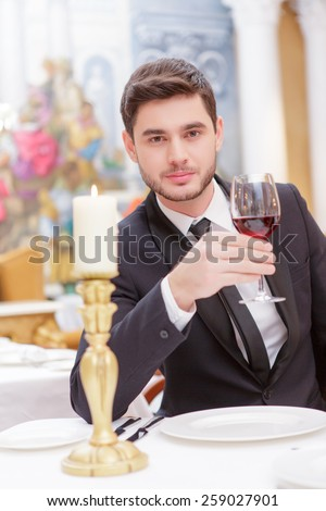 Making a toast. Handsome young man in suit raising his glass of wine while making a toast in luxury restaurant  - stock photo