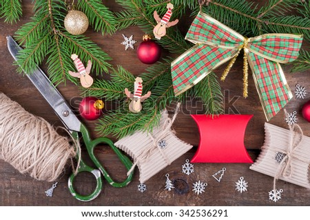 Making and decorate handmade christmas gift boxes on wooden table background. Christmas tree branch, snowflakes, christmas ornaments, string and scissors top view - stock photo