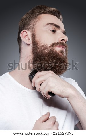 Making beard perfect. Confident young bearded man shaving with electric razor while standing against grey background - stock photo