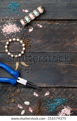 Making bracelet. Beads, plier, glass hearts and accessories to create hand made jewelry on wooden table. Top view - stock photo