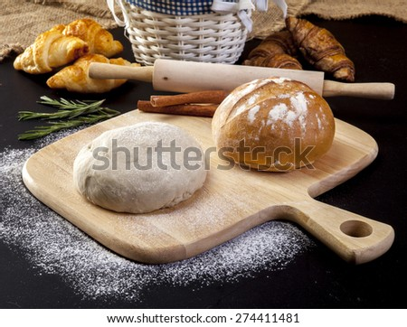 Making bread on table on wooden background - stock photo