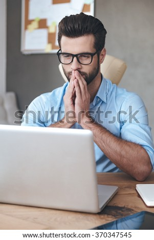 Making business decision every day. Close-up pensive young handsome man wearing glasses working on laptop and keeping hands on chin while sitting at his working place