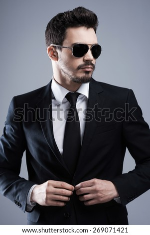 Making business look good. Handsome young man in formalwear and sunglasses buttoning his jacket and looking away while standing against grey background - stock photo