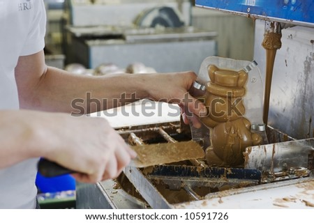 making chocolate bunny in a bakery. close-up of hands. - stock photo