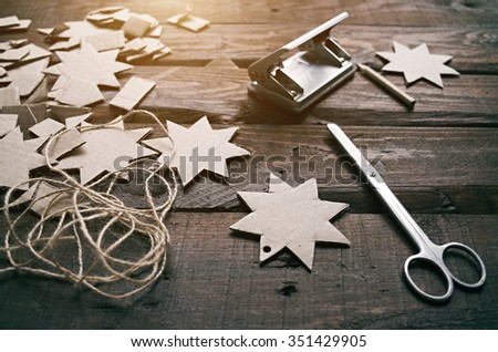 Making Christmas cardboard gifts garlands on old wooden table. Winter holidays new year vintage crafting. - stock photo