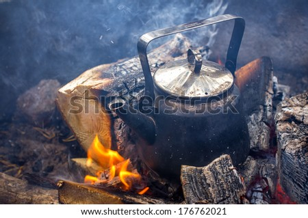 Making coffee in the fireplace when hiking in the nature is the most relaxing activity you can do. - stock photo