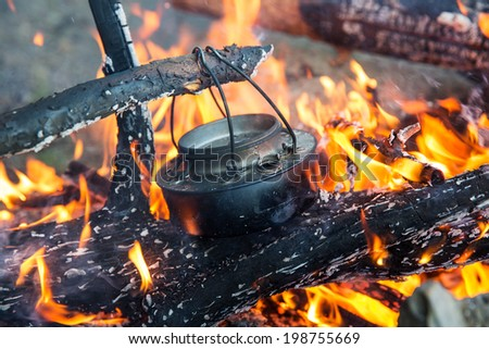 Making coffee on camp fire - stock photo