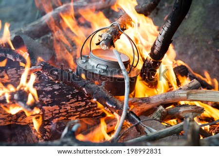 Making coffee on camp fire in the woods - stock photo